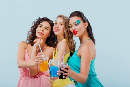 three girls girlfriends happy with hairstyle and makeup unusual, is holding plastic cups of juice, look at the camera, isolated blue background, positive facial emotions, copy space