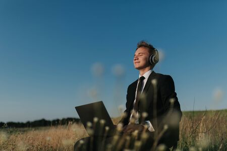 young businessman with headphones listening music in field, sitting on chair, using laptop, closed eyes, outdoor Reklamní fotografie