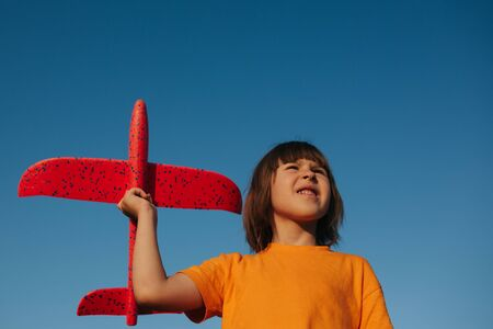 happy little girl holds a red airplane in the red jersey, outdoors, sky background, copy space