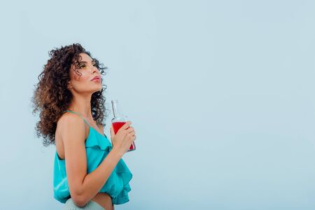 fashionable lady smiles has the drink bottle in her hand, dressed in blue shirt, looks up isolated on blue background, copy space