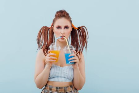 young girl hairstyle and makeup unusual is holding two plastic cups of juice, isolated blue background, positive facial emotions, copy space