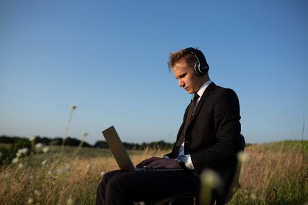 young man with headphones using laptop, in field, sitting on chair, in suit, outdoor Reklamní fotografie