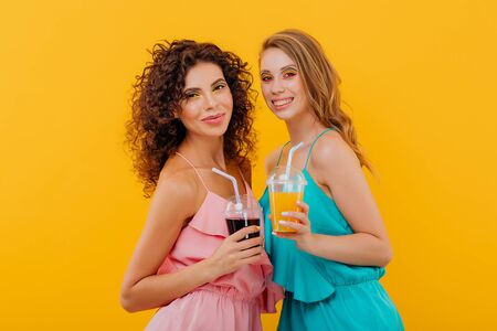 fashionable two cheerful girls with curly hair, hold the plastic cup with juice, look at the camera positive facial emotions, isolated on yellow background, copy space