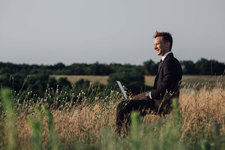 Young happy businessman on meadow,  sitting in the chair, using a laptop, outdoor, profile view