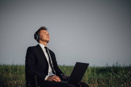 young guy with headphones listening music in field, sitting on chair, using laptop, closed eyes, outdoor Reklamní fotografie