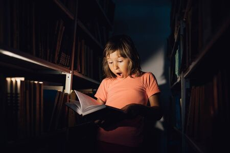 little child reads the book, is scared, has open mouth. holds a book in his hand, learns in the library, indoors Reklamní fotografie