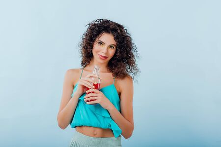 beautiful and fashionable lady smiles at the camera with curly hair, has the drink bottle in her hand, positive facial emotions, isolated on blue background, copy space Reklamní fotografie