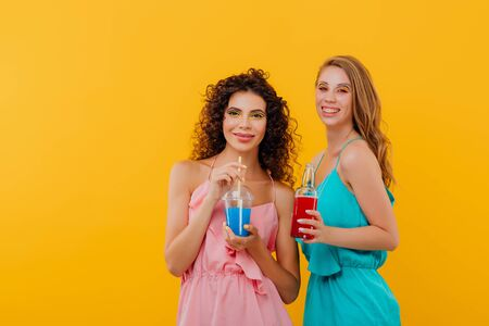 two beautiful girls with curly hair drink bottle in hand and plastic cup with juice, look at the camera, positive facial emotions, isolated on yellow background, copy space Reklamní fotografie