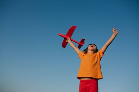 emotionally little girl playing with a toy airplane outdoor, dreams of flying, outdoors, sky background, copy space