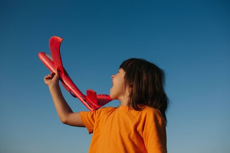 little girl holds a red plane in her hand, outdoors, sky background, copy space