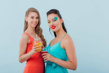 two beautiful girls hairstyle, makeup unusual, they drink in hand, looking at the camera, positive facial emotions, isolated on blue background, copy space