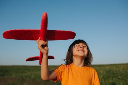 Adorable little girl holding a toy plane outdoors on sunny summer day, outdoors, sky background
