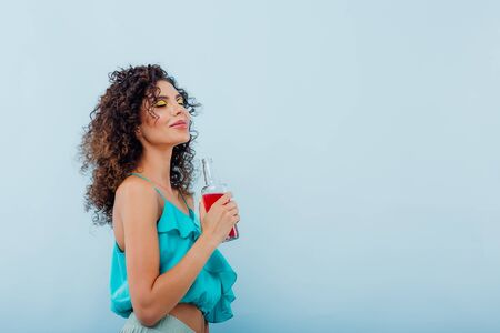 fashionable young girl smiles has bottle with drink in hand, dressed in blue shirt, eyes closed, positive facial emotions, isolated on blue background, copy space Reklamní fotografie
