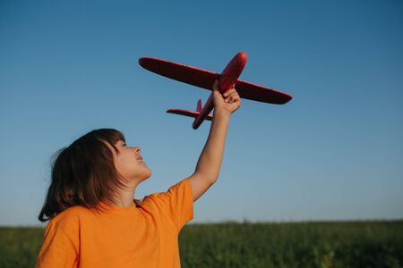 little girl holds a red plane, dressed in a red shirt, dreams of flying, outdoors, sky background Reklamní fotografie