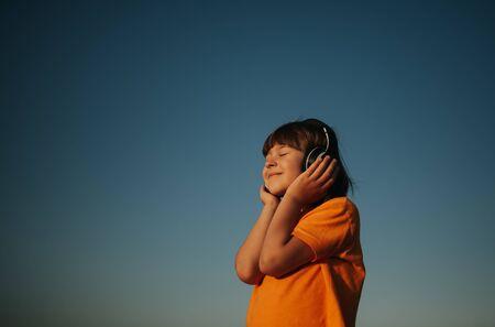 The lovely little girl, against the blue sky, listens to music through headphones, outdoors, sky background Reklamní fotografie