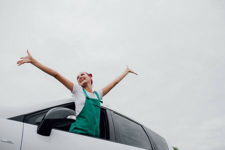 Car woman on road on road trip waving happy smiling out the window, outdoor