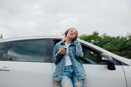 teenager relax with headphones. has eyes closed, listens to music, has the drink bottle in his hand. next to the car, outdoor Reklamní fotografie