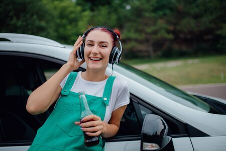 happy young girl with headphones. listen to music, have drink bottle in hand. looking into the camera, Besides car,  outdoor
