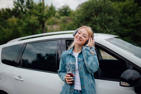 teens, relax with headphones. has eyes closed, listens to music, has the drink bottle in his hand. Besides car,  outdoor
