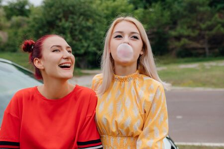 two teenagers blowing up a bubble of a chewing gum dressed in red and yellow dresses, Besides car,  outdoor