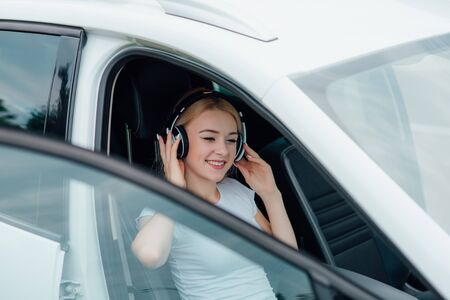 happy teenager with headphones listening to music, sitting in car,  outdoor