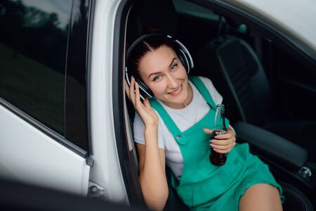 young girl with headphones, listen to music, smile is happy, has bottle with drink in hand. sitting in the car. looks at the camera, outdoor Reklamní fotografie