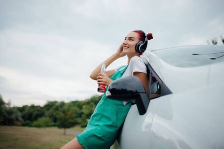 happy young girl with headphones. listen to music, have drink bottle in hand. copy space, next to the car, outdoor, profile view 版權商用圖片