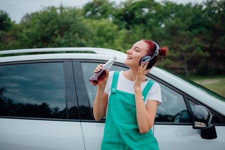 happy teens with headphones. has the drink bottle in his hand. next to the car, outdoor Reklamní fotografie