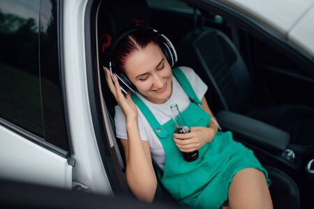 young girl with headphones, listen to music, happy, has bottle with drink in her hand. sitting in the car, outdoor