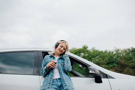 portrait of a happy teenager. with headphones. listen to music, have drink bottle in hand. copy space, Besides car,  outdoor
