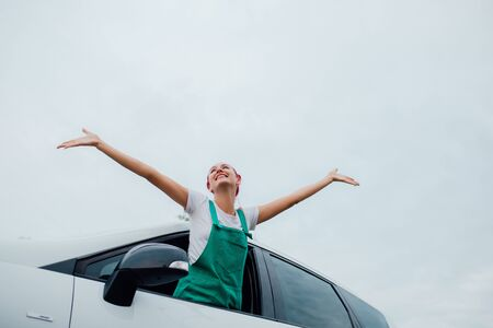 oung woman relax and happy on summer road trip travel vacation leaning out car window on blue sky, outdoor Reklamní fotografie