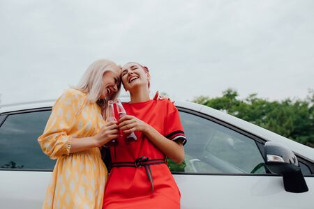 two teenagers are cheerful, having fun in red and yellow dresses, has the drink bottle in his hand. Besides car,  outdoor Reklamní fotografie