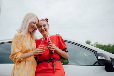 two girlfriends are cheerful, having fun in red and yellow dresses, has the drink bottle in his hand. next to the car, outdoor