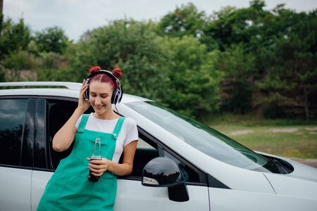 happy teenager. with headphones. listen to music, have drink bottle in hand. copy space, next to the car, outdoor