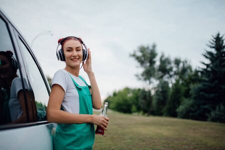 happy teens with headphones. listen to music, have drink bottle in hand. looking into the camera, Besides car,  outdoor