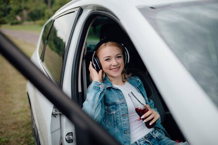 happy teenager with headphones. looks at the camera, has the drink bottle in his hand. sitting in the car. outdoor Reklamní fotografie