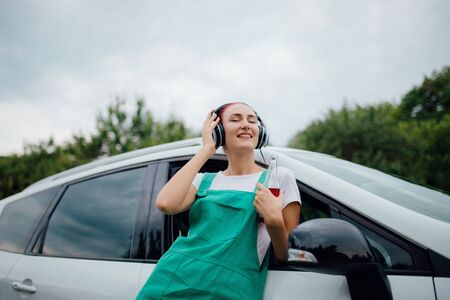 happy and relaxed teenager with headphones. listen to music, have drink bottle in hand. copy space, Besides car,  outdoor