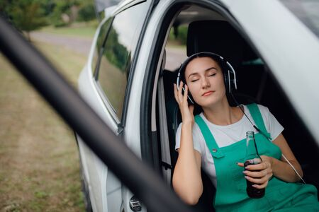 teenager relaxes  with headphones on head. has eyes closed, has the drink bottle in his hand. sitting in the car. outdoor