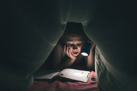 surprised little girl is read a book under a blanket with a flashlight in a dark room at night, in bed, ton