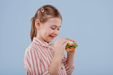 little girl with sandwich in hand. profile view, Imagens