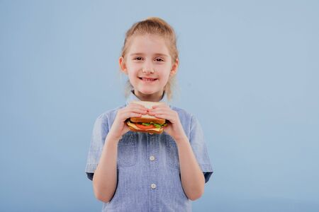 little girl with sandwich in hand. girl looks at the camera,