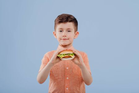 child boy with sandwich in hand. looks at the camera, Imagens