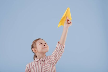 girl plays with yellow paper plane, looks at the camera, Foto de archivo