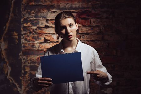 Confused woman pointing at document, brick wall