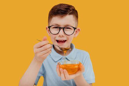 Happy boy eating fresh honey against yellow background