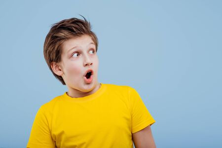 scared boy looks at camera in yellow t-shirt
