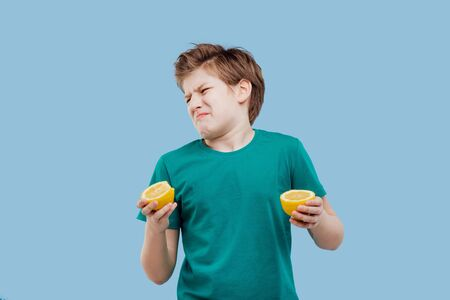 gentil garçon goûte un citron frais, goût aigre, Banque d'images