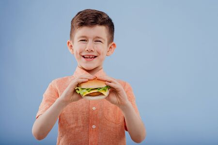 little boy smiles with sandwich in hand.