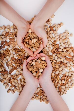 top view Mixed nuts in the four child hands walnut, pistachio, almonds, Hazelnuts, on white background,