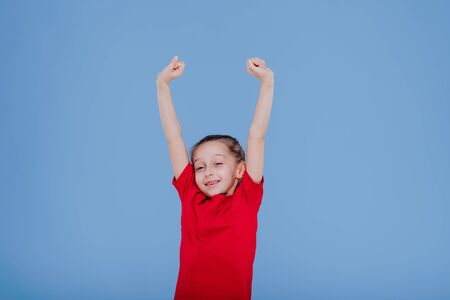 happy little girl in red outfit raising arms and jumping while having fun and celebrating success in studio with blue background